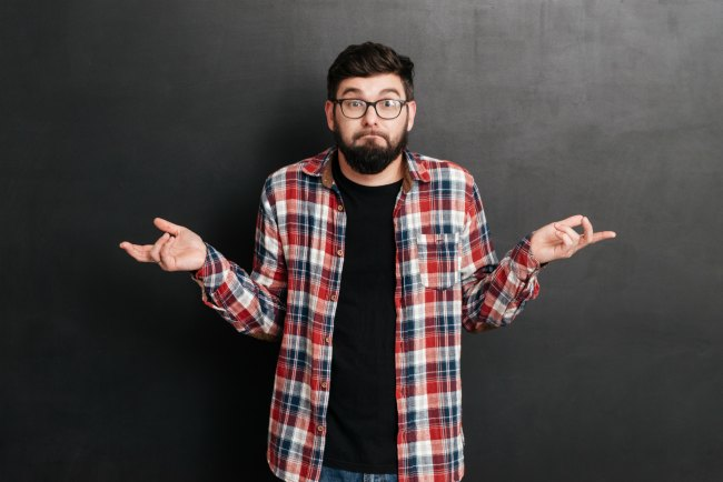 Confused bearded young man in glasses shrugging his shoulders