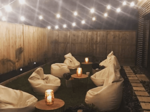 gold bean bags with timber top coffee tables and gold lamps in backyard