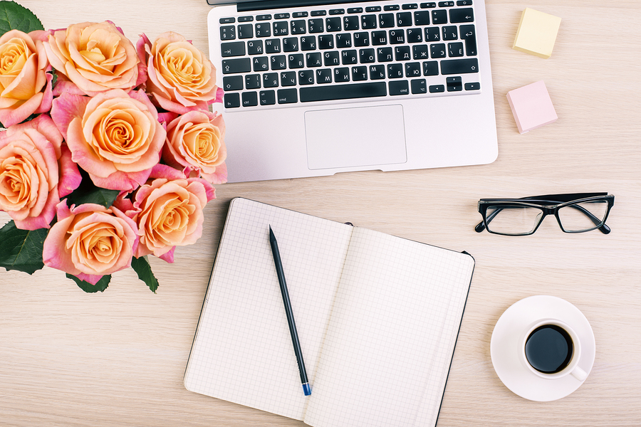Top view of creative woman's desktop with open notepad pencil glasses coffee cup roses and laptop keyboard