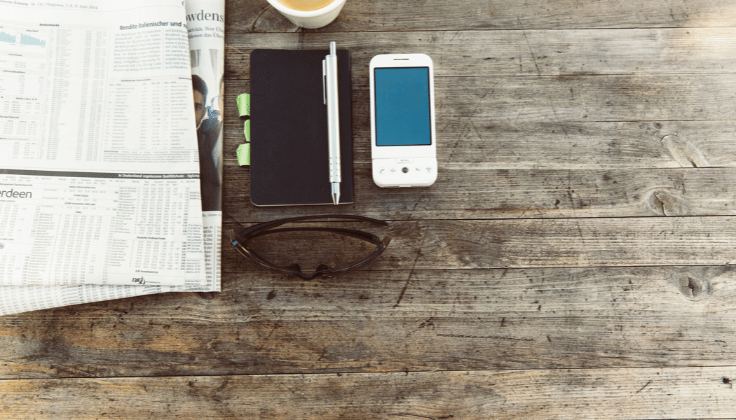 Rustic desk with newspaper, notebook and phone
